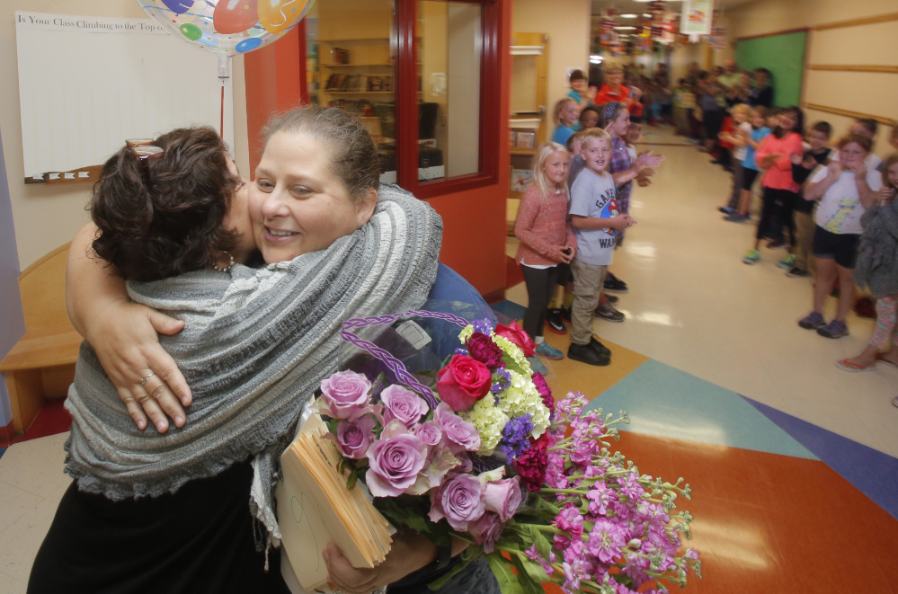 Stevens gets a hug from Principal Bonnie Hicks while receiving a schoolwide welcome home on Monday morning.