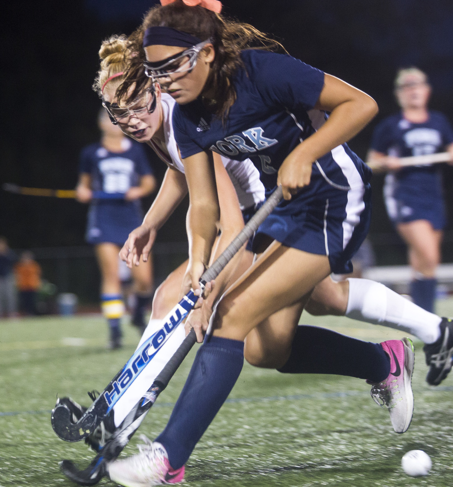 Yarmouth senior Liza Lunt, left, battles York freshman Cassie Reinertson for the ball Monday in Yarmouth. York scored twice in the second half to win 3-1. It was the 44th straight win for the Wildcats. Brianna Soukup/Staff Photographer