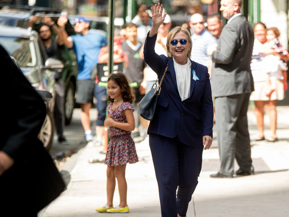 Democratic presidential candidate Hillary Clinton, seen waving Sunday, left the 9/11 anniversary ceremony in New York early after feeling