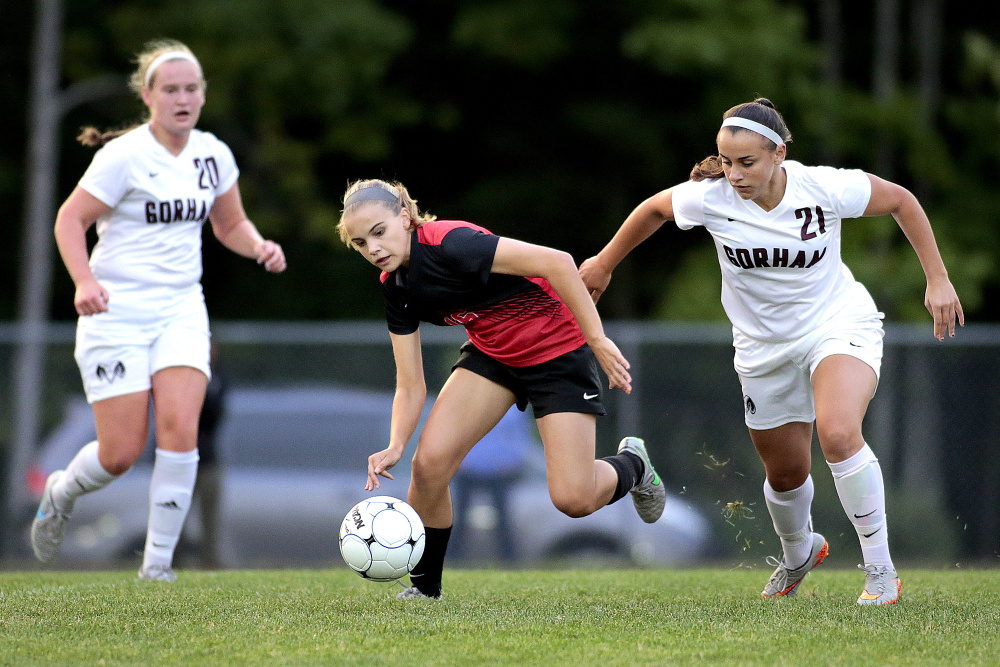 SEPT. 14: Scarborough's Natalie Russell tries to keep her balance while chasing after the ball as Gorham's Michelle Rowe and Noelle DiBiase give chase during the first half of a soccer game at Gorham.