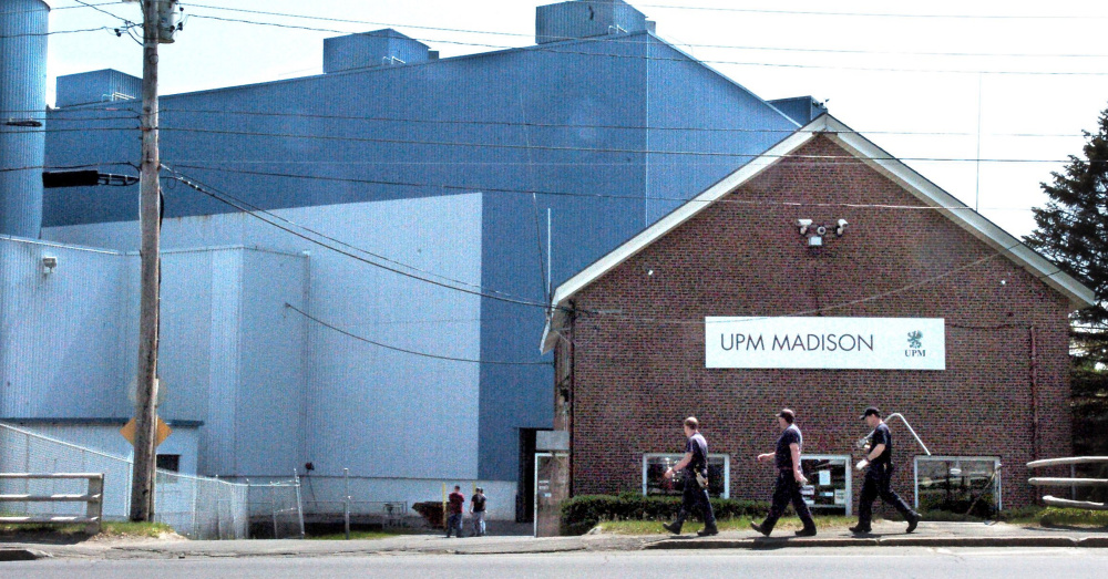 Millworkers carry tools into the Madison Paper Industries mill in Madison in May.