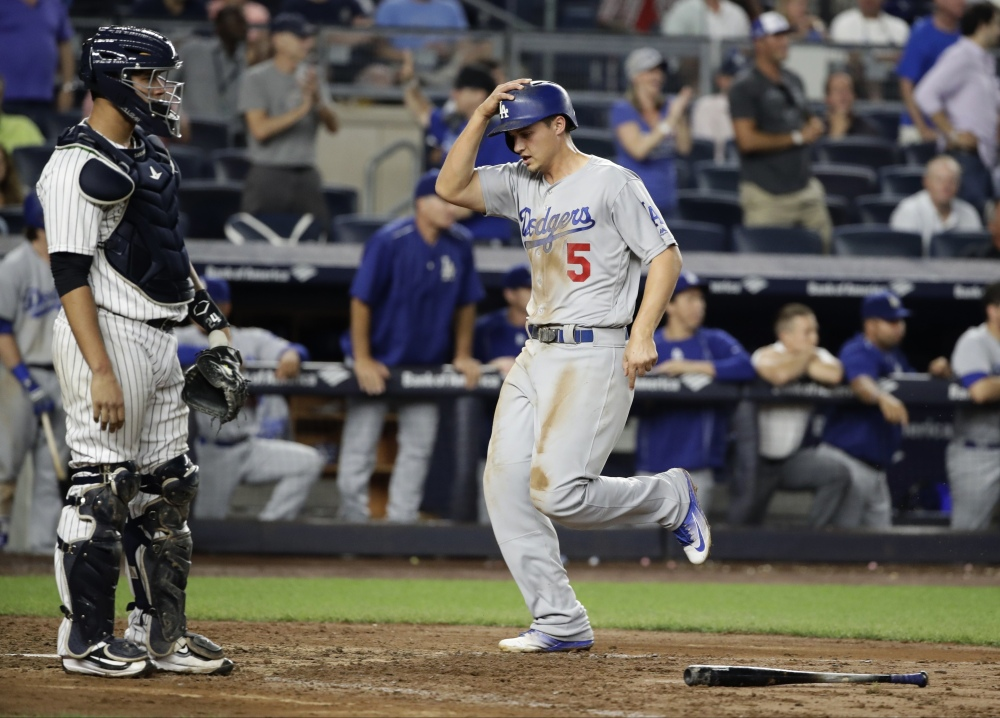 The Dodgers' Corey Seager scores in front of Yankees catcher Gary Sanchez during the ninth inning of a 2-0 Los Angeles win at New York on Wednesday.