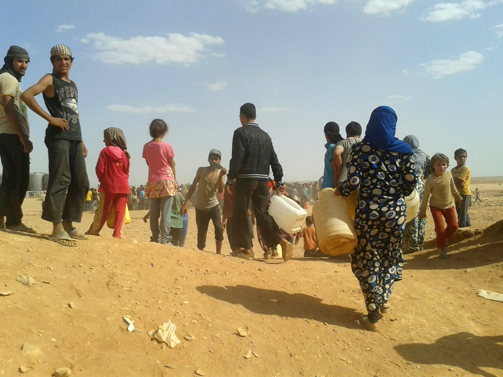 Syrian refugees gather for water at the Rukban refugee camp in Jordan's northeast border with Syria in June. Of the millions of exiles from the Syrian war, only about 10,000 have reached U.S. shores.
