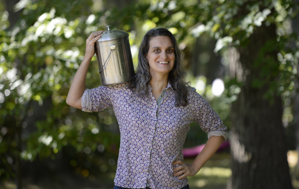 Lisa Botshon, a professor at the University of Maine at Augusta, with her compost bucket. Composting reduces the amount of garbage being sent to landfills.