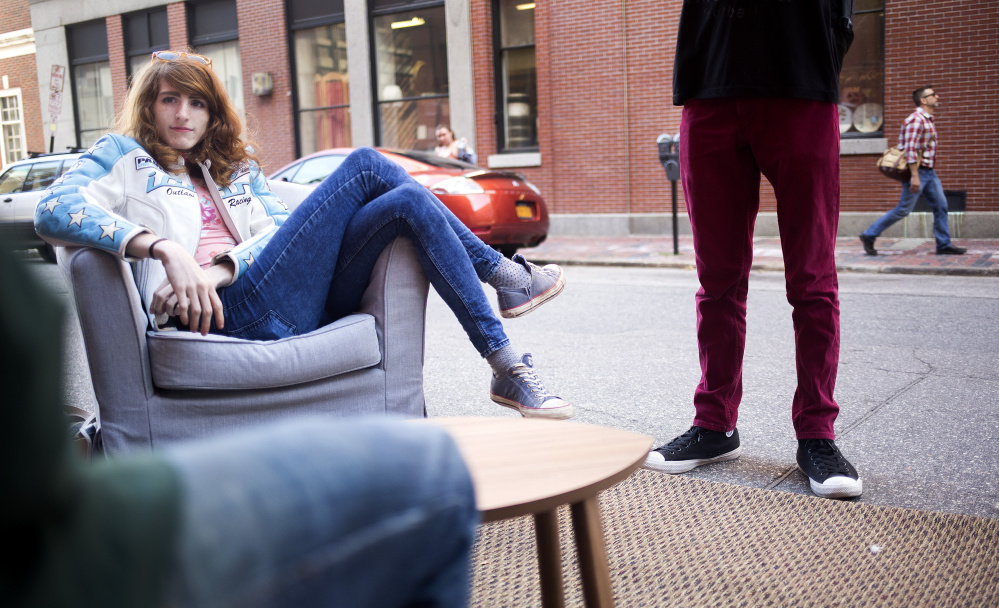 """PORTLAND, ME - SEPTEMBER 16: Rose Bloem, a sophomore at MECA, relaxes in a parking spot """"living room"""". The parking spot was transformed by Think Tank Coworking for PARK(ing) Day 2016. Parking spots were temporarily reclaimed and converted into public space. The day, which is celebrated all over the world, is meant to challenge people to rethink the use of our streets as public space. (Photo by Brianna Soukup/Staff Photographer)"""