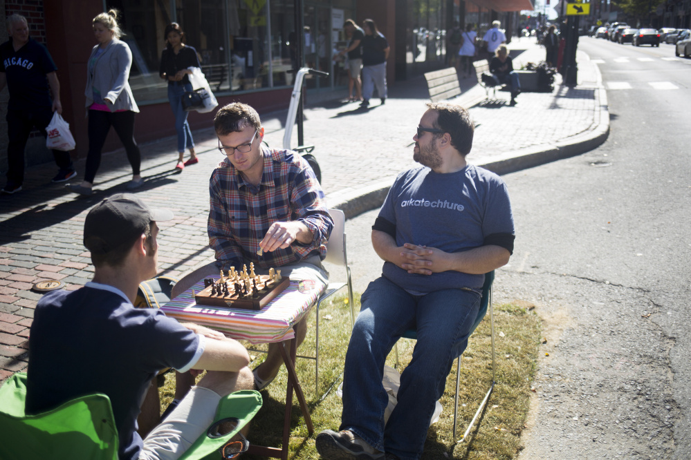 PORTLAND, ME - SEPTEMBER 16: From left, Skye Priestley and Chris Bond, of Portland, play chess in a parking spot on Congress Street that was transformed by Hack Portland and Code for Maine for PARK(ing) Day 2016. Parking spots were temporarily reclaimed and converted into public space. The day, which is celebrated all over the world, is meant to challenge people to rethink the use of our streets as public space. (Photo by Brianna Soukup/Staff Photographer)