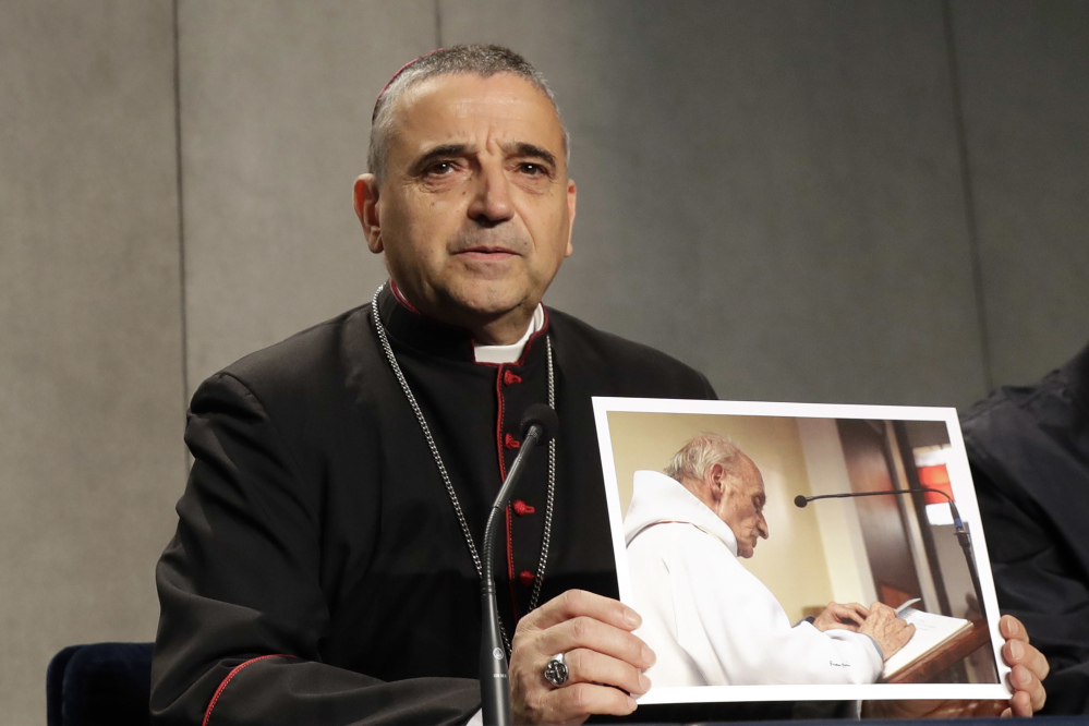 Rouen Bishop Dominique Lebrun shows a photo of the Rev. Jacques Hamel during a news conference at the Vatican on Wednesday. Pope Francis honored the French priest who was killed by Islamic extremists while celebrating Mass as a martyr and urged all people of faith to have the courage to denounce such killings as