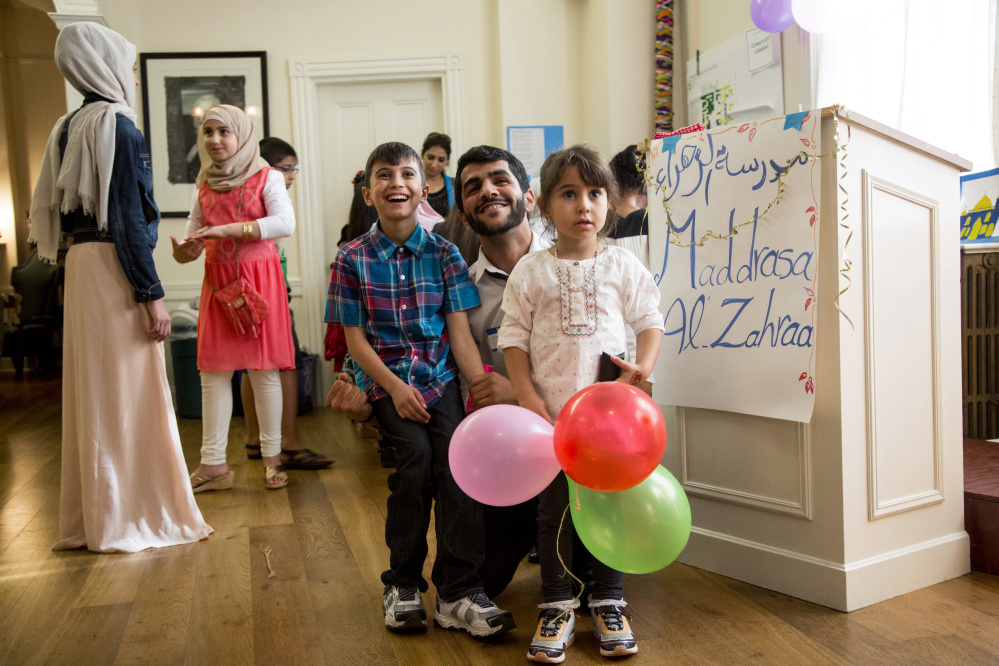 Mohammed Albehadli, a former teacher at the Alzahraa Arabic School, poses for a photo with students Zayyd Najar, 9, left, and Rawan Najar, 4, at an Eid al-Adha celebration in Portland on Saturday. Mohammed drove back to Portland from college in Connecticut to attend the celebration.