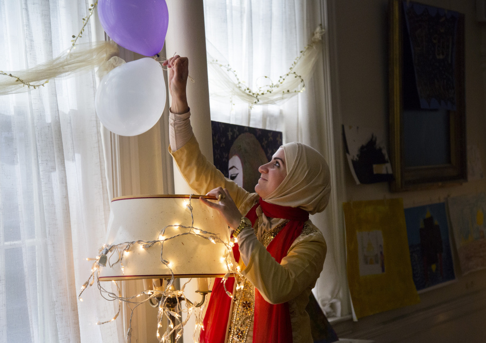 Mayasah Al Hashimi of Westbrook takes down balloons for the kids to play with after the Eid al-Adha festivities.