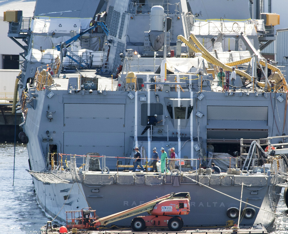 Shipbuilders walk across the aft deck of an Arleigh Burke destroyer that's currently under construction at Bath Iron Works in Bath. More than 6,000 workers are employed here, the yard's highest level in more than a decade, but losing a lucrative cutter contract is expected to reduce that number in time.