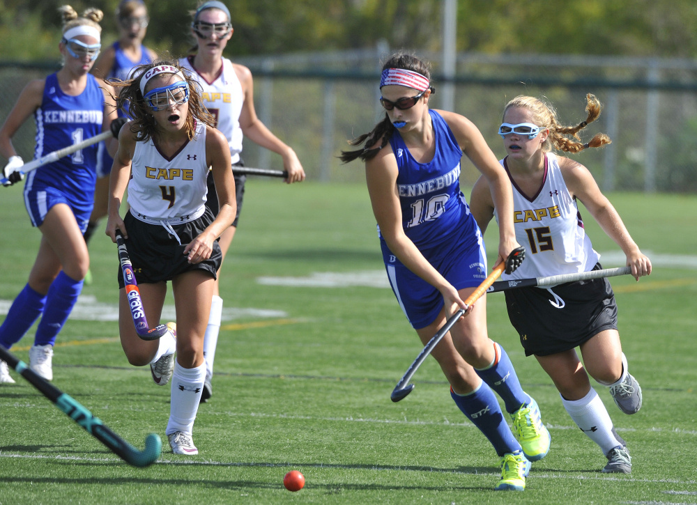 Grace Grenier, center, of Kennebunk is pursued by Julia Lennon and Erika Miller of Cape Elizabeth during their Western Maine Conference field hockey game Saturday. Kennebunk won, 8-1.