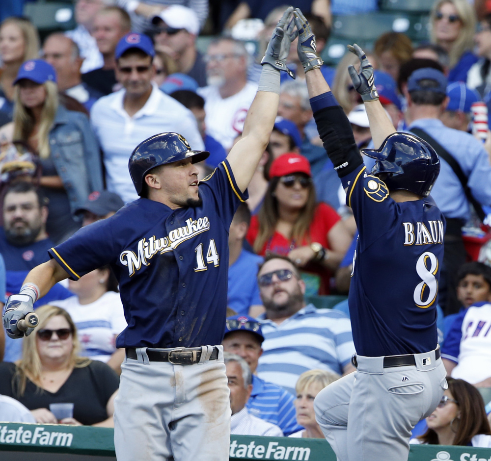 Milwaukee's Ryan Braun, right, celebrates with Hernan Perez after hitting a two-run homer in the sixth inning of the Brewers' 11-3 win against the Cubs in Chicago.