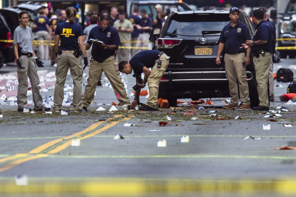 Members of the Federal Bureau of Investigation (FBI) carry on investigations at the scene of Saturday's explosion on West 23rd Street and Sixth Avenue in Manhattan's Chelsea neighborhood, New York, Sunday, Sept. 18, 2016. An explosion rocked the block of West 23rd Street between Sixth and Seventh Avenues at 8:30 p.m. Saturday. Officials said more than two dozen people were injured. Most of the injuries were minor.