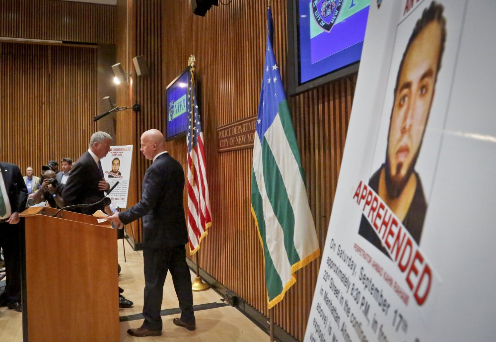 Mayor Bill de Blasio, left, and New York Police Department Commissioner James O'Neill arrive for a news conference to announce the arrest of bombing suspect Ahmad Kahn Rahami, whose photo is shown on a display at right, on Monday at police headquarters in New York.