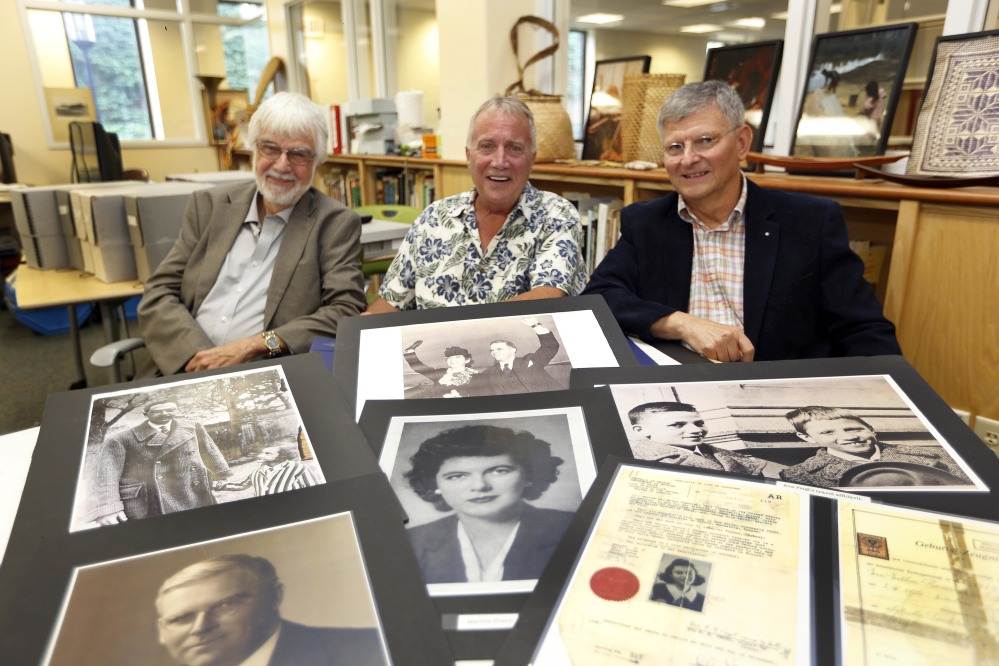 Keene, N.H., State College professors, from left, Lawrence Benaquist, Tom Durnford and Paul Vincent, sit behind photos that they used to research a Massachusetts couple who helped Jewish refugees flee the Nazis during World War II.