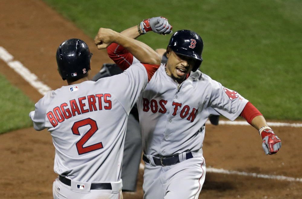 Mookie Betts celebrates with Xander Bogaerts after driving in Bogaerts on a home run on Sept. 19 in Baltimore, where the Red Sox swept the Orioles on their march to the top of the AL East.