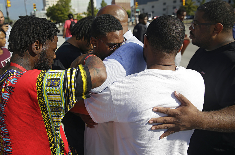Protesters pray with Tyler Johnson (wearing glasses), son of Terence Crutcher, in front of the county courthouse Monday in Tulsa, Okla., during a demonstration after the police shooting of Crutcher Friday.