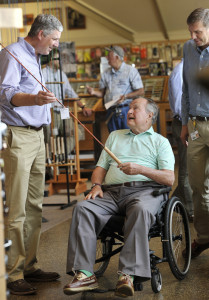 Former President George H.W. Bush looks over a fishing rod with Shawn Gorman, left, board chairman at L.L. Bean, during Bush's visit to the retail store in Freeport on Tuesday.