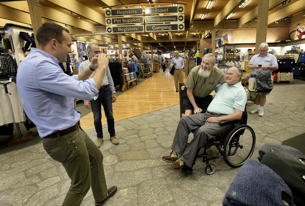 Evan Sisley, left, an aide to former President George H.W. Bush, seated, captures a memorable moment for Jerry Furr of Charlotte, N.C., at L.L. Bean in Freeport.