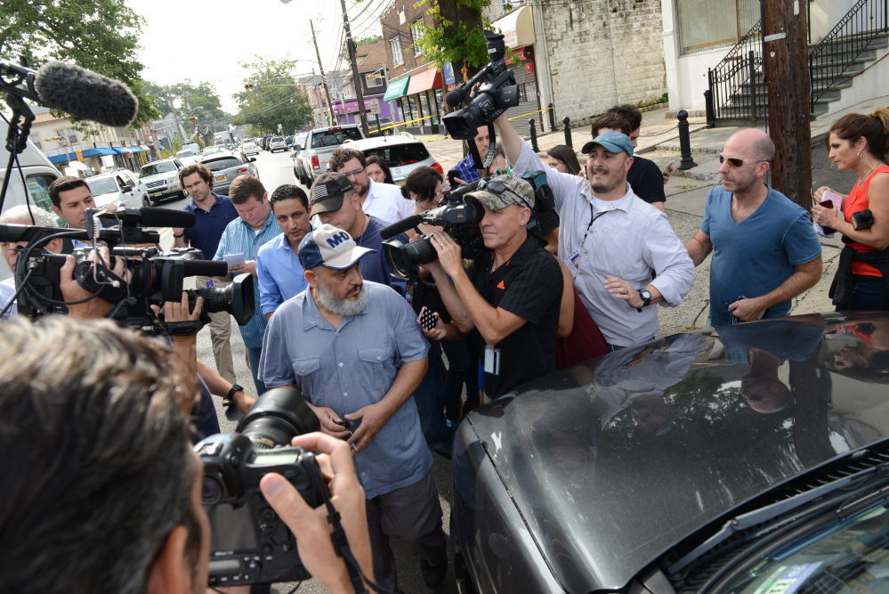 The father of Ahmed Rahami, Mohammad Rahami, center left, comes out from his home through a crowd of media to get to his vehicle on Tuesday in Elizabeth, N.J . Mohammad Rahami contacted the FBI two years ago with concerns his son was a terrorist, a law enforcement official said Tuesday. But the father later retracted the claim.