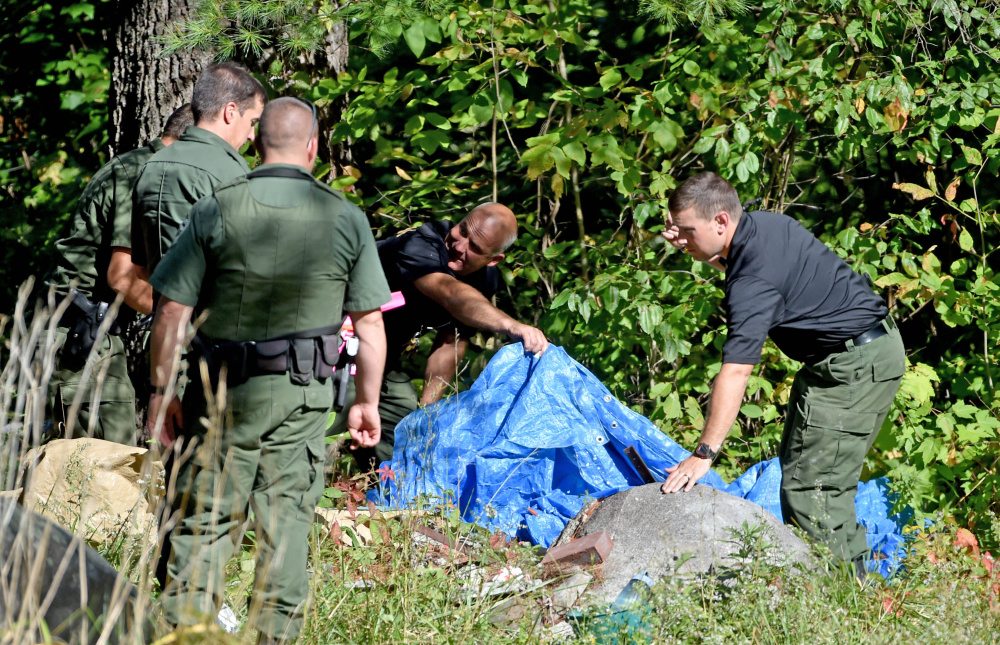 Investigators with the Maine State Police and Maine Warden Service look for evidence in the death of a woman whose body was found in the woods behind 628 Norridgewock Road in Fairfield on Tuesday.