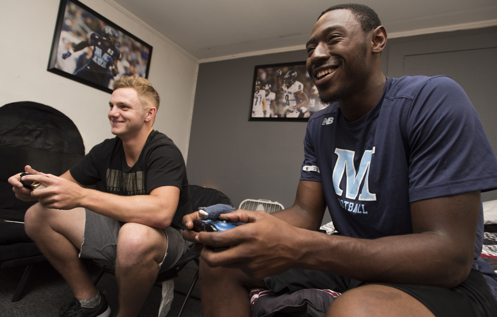 Maine quarterback Dan Collins, left, and receiver Jaleel Reed have built a friendship not just through football but long rides between Orono and the Philadelphia area. And, of course, their love of video games, especially FIFA, the EA soccer game.