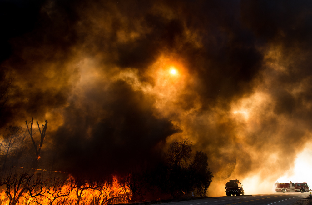 Firefighters battle a wildfire as it crosses Cajon Boulevard in Keenbrook, Calif., on Aug. 17. From June to August, there were at least 10 different weather disasters that each caused more than $1 billion in losses.