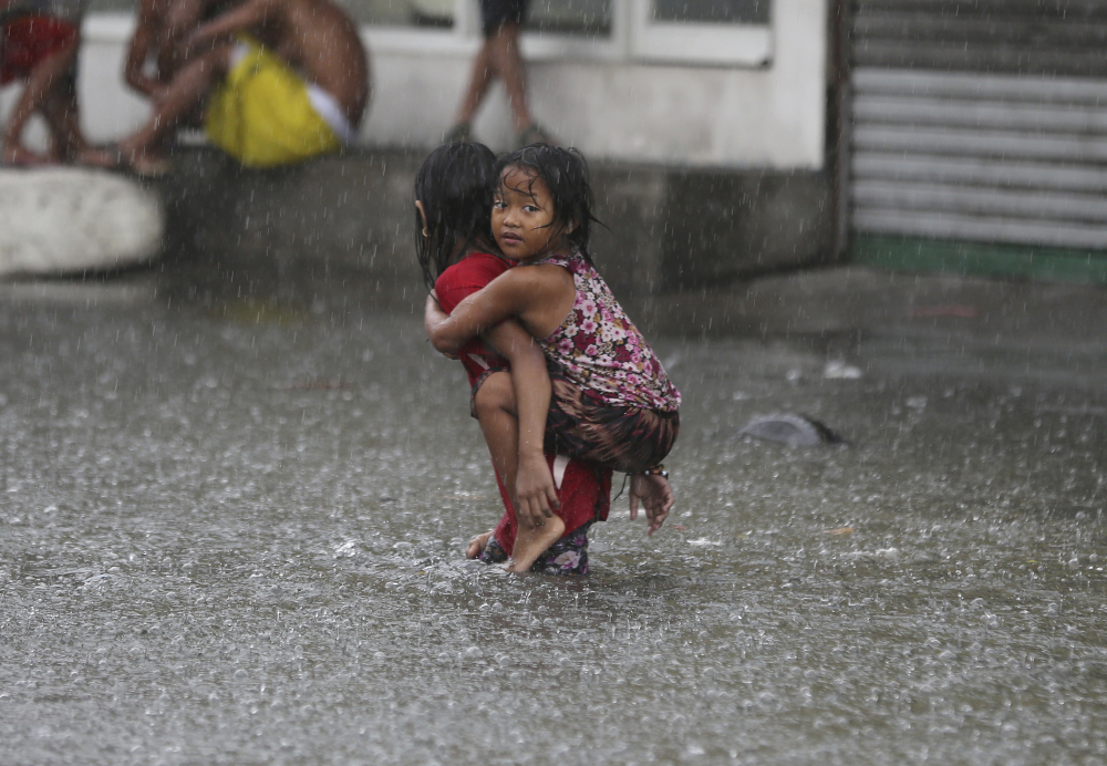 A Filipino girl is carried along a flooded road on July 8 in suburban Mandaluyong, east of Manila, Philippines, as downpours intensify while Typhoon Nepartak exits the country.
