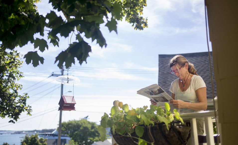 JoAnn Dowe looks at published renderings of the development proposed for the eastern waterfront at her house on Waterville Street, overlooking Portland Harbor.