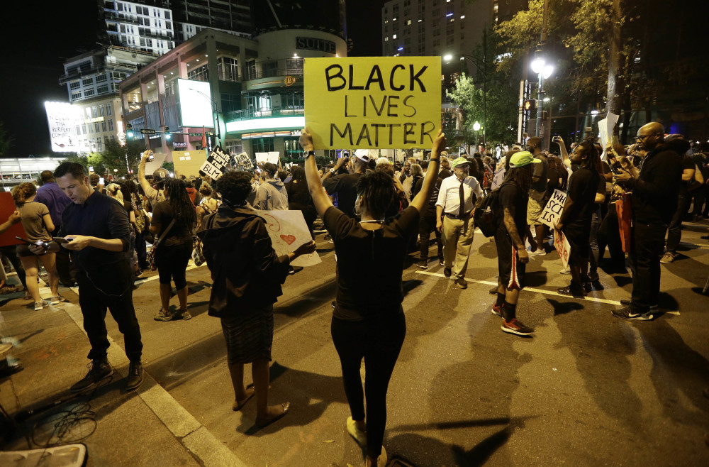 People take to the streets of Charlotte on Thursday night during a peaceful march protesting Tuesday's police shooting of Keith Lamont Scott