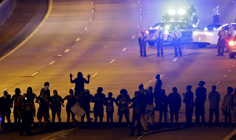 Protesters block Interstate 277 in Charlotte on Thursday night, the third night of unrest following Tuesday's police shooting of Keith Lamont Scott. The demonstration halted traffic before officers in riot gear fired pepper balls at the protesters.