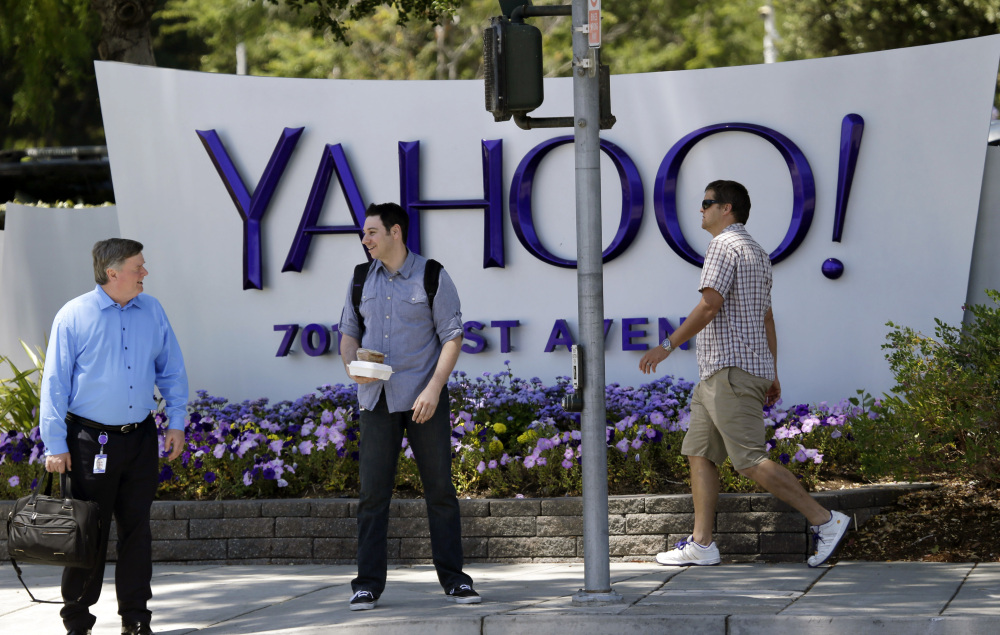 People walk in front of a Yahoo sign at the company's headquarters in Sunnyvale, Calif., in 2014. Yahoo on Thursday confirmed a data breach that dates back to late 2014.