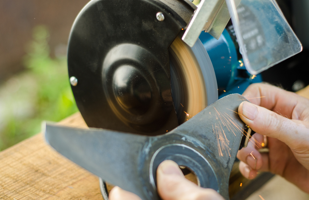 Sharpening your tools – like a lawn mower blade – makes the work go easier. Luckykot/Shutterstock.com