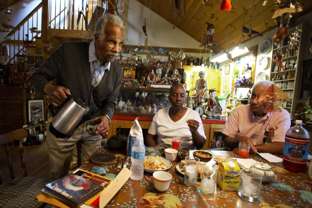 Artist Ashley Bryan, 91, pours coffee for his guests, including good friends Joyce Taylor Gibson and Roland Gibson, in the dining room of his home this summer. Photo by Gabe Souza/Staff Photographer
