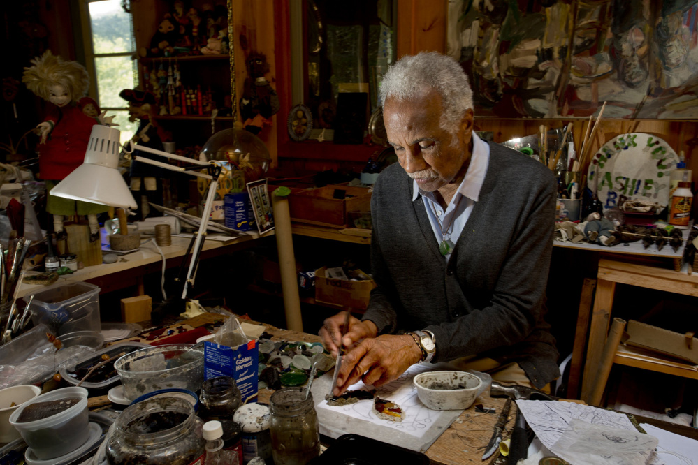 Artist Ashley Bryan, then 91, works with sea glass to make art at his workshop on Little Cranberry Island in 2014. Bryan has visited the island to create art since 1946 and retired there in the 1980s.