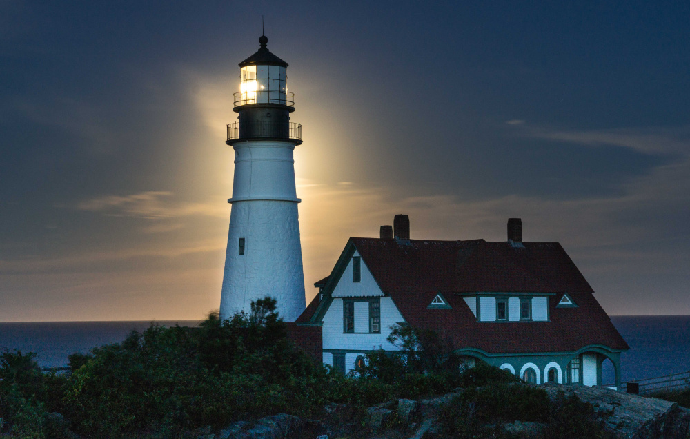 Portland Head Light in Cape Elizabeth is all aglow on Sept. 16, silhoutted by the rising full moon, as captured by Craig C. Shaknis of Naples.