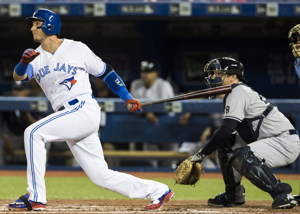 Toronto's Troy Tulowitzki hits a two-RBI single as New York catcher Austin Romine watches during the first inning of the Blue Jays' 9-0 win Friday night in Toronto.