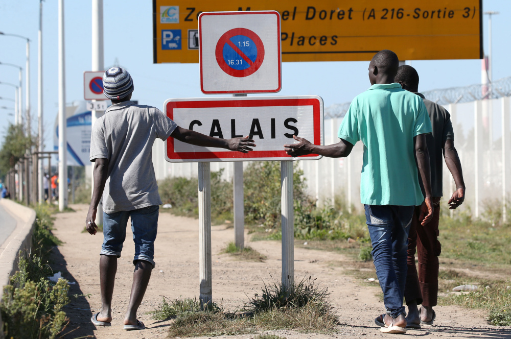 Migrants pass by a road near the camp called