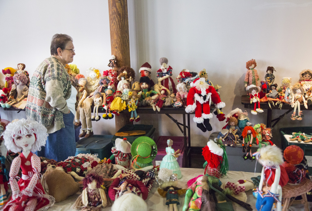 Liette Morin of Lewiston looks through dolls from the collection of Bertha Chasse during a sale at Museum L-A. Derek Davis/Staff Photographer