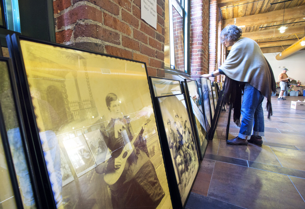 "Joan Vermette of Hollis looks through photographs from a past exhibit titled ""The Power of Music"" during a sale at Museum L-A on Saturday. Derek Davis/Staff Photographer"