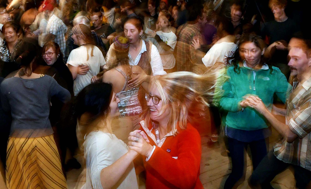 Volunteers let loose during the annual contradance at the 40th annual Common Ground Country Fair in Unity on Saturday.