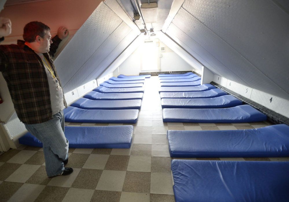 Portland Shelter Director Robert Parritt checks over a room at the Oxford Street Shelter in 2013. Small rooms at the city's shelters are seen as unsafe.