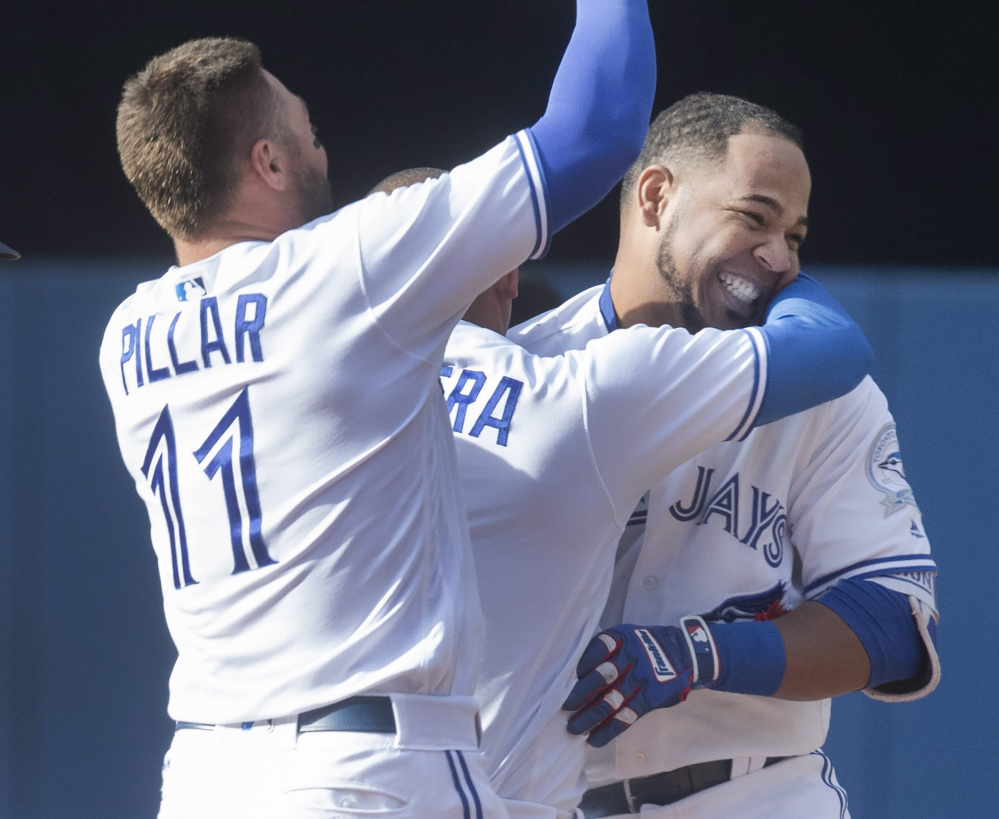 Edwin Encarnacion, right, is mobbed by Blue Jays teammates Kevin Pillar, left, and Ezequiel Carrera after his winning single in the ninth inning Sunday.