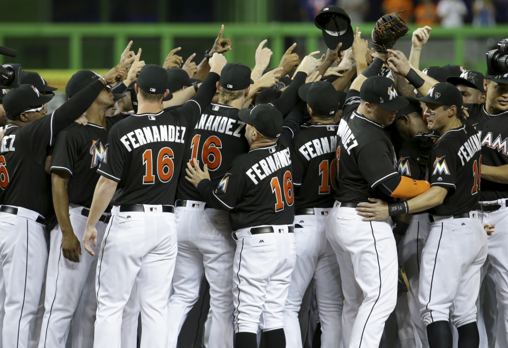 Miami Marlins players and coaches, all wearing Jose Fernandez's uniform No. 16, gather around the mound prior to Monday's game against the New York Mets at Miami.