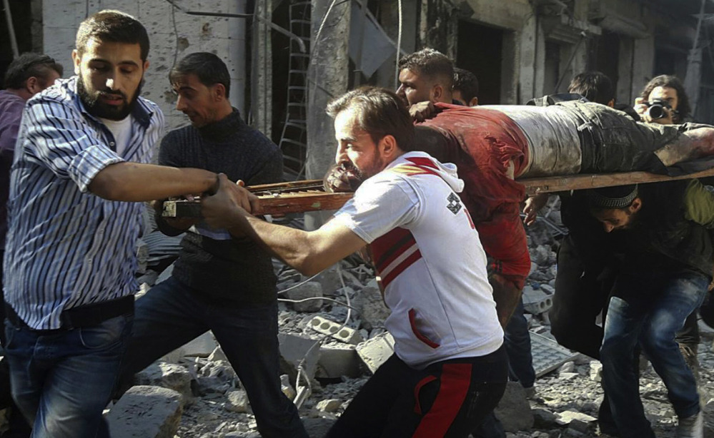 In this photo provided by the Syrian Civil Defense group known as the White Helmets, Syrians carry a victim after airstrikes by government helicopters on the rebel-held Aleppo neighborhood of Mashhad, Syria, Tuesday Sept. 27, 2016. With diplomacy in tatters and a month left to go before U.S. elections, the Syrian government and its Russian allies are using the time to try and recapture the northern city of Aleppo, mobilizing pro-government militias in the Old City and pressing ahead with the most destructive aerial campaign of the past five years. (