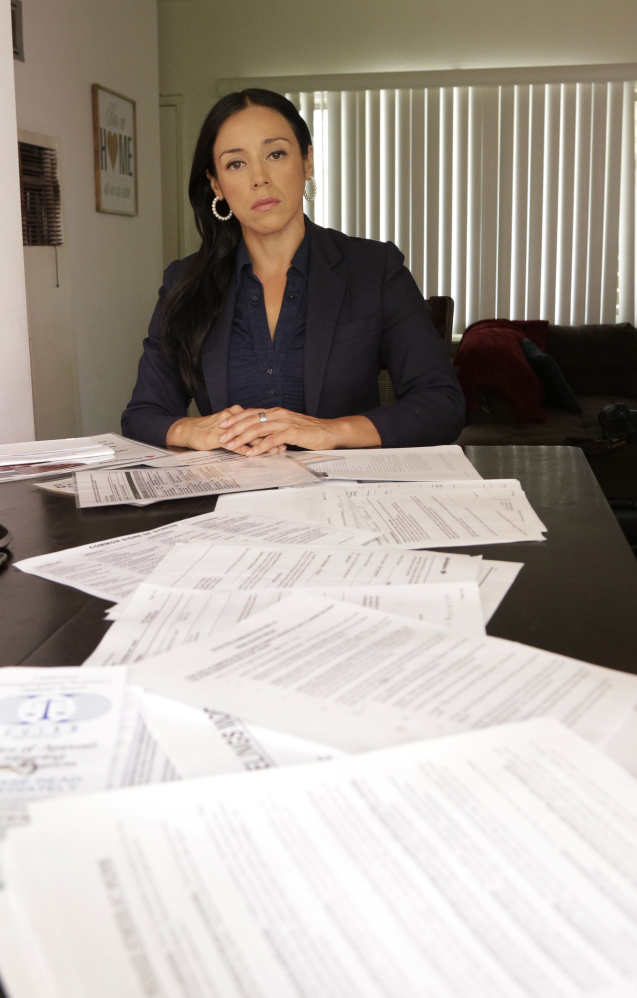 Ruth Landaverde, a former worker at Wells Fargo and Bank of America, displays documents supporting her allegations of unrealistic sales goals, at her home in Glendale, Calif. She's one of many former employees who say retail banks have become high-pressure sales centers.