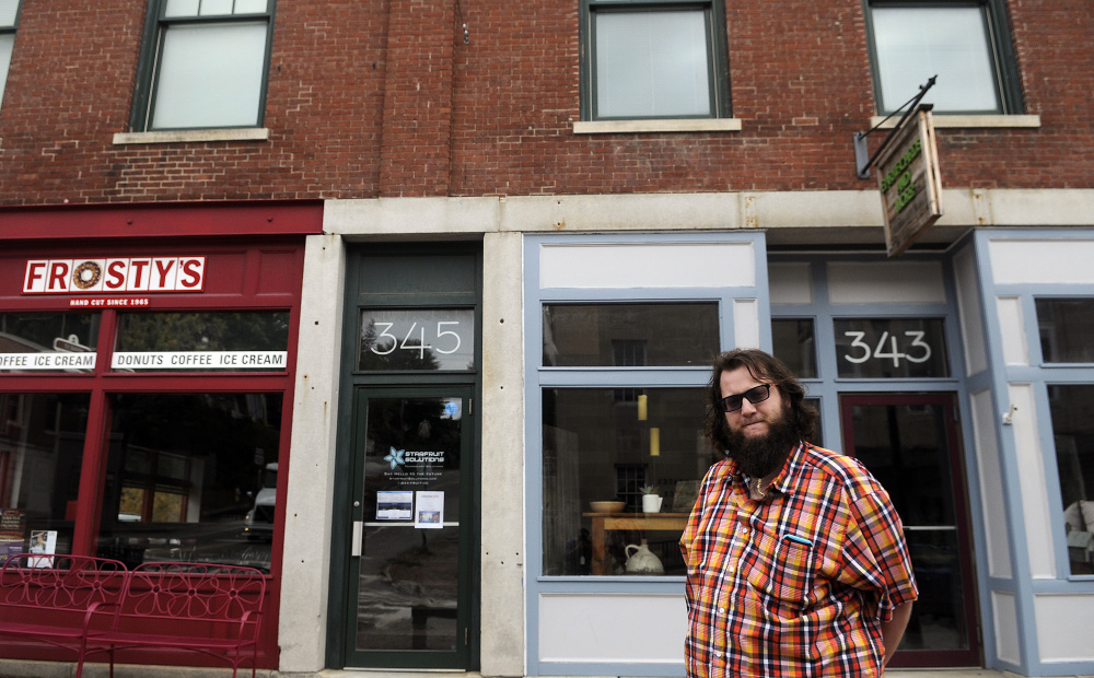 Brad-Lee Nichols stands on Tuesday outside 345 Water St. in Gardiner, where he has opened a co-working space on the second floor. His firm, Starfruit Solutions, which builds websites and apps, provides a professional office to those who need just a bit of space.