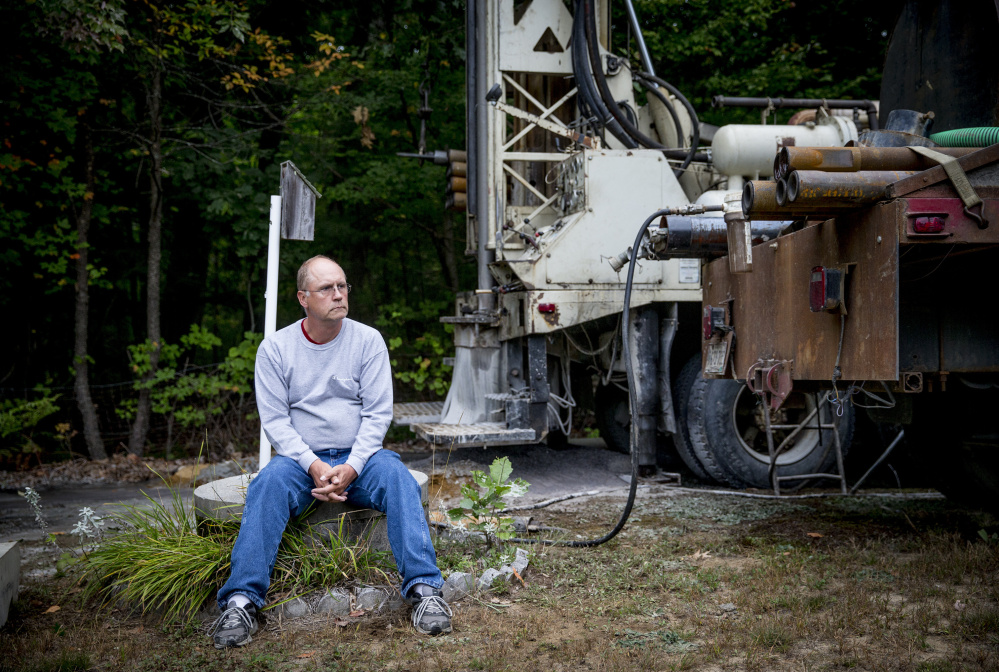 With a new well being drilled on his property in Standish, Bob Boynton sits atop the concrete casing of his shallow dug well, which ran dry a week ago as southern Maine and much of New England endure the region's worst drought in more than a decade.