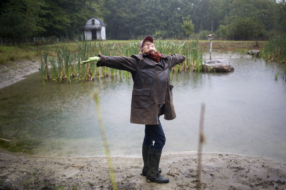 Nina Fuller welcomes the brief rain Tuesday morning near a pond at her farm in Hollis. When Fuller's well ran dry last week, she panicked, not knowing how she would get water to her horses, sheep and goats. Work on her well has given her temporary relief, and she's been prioritizing resources for her animals.
