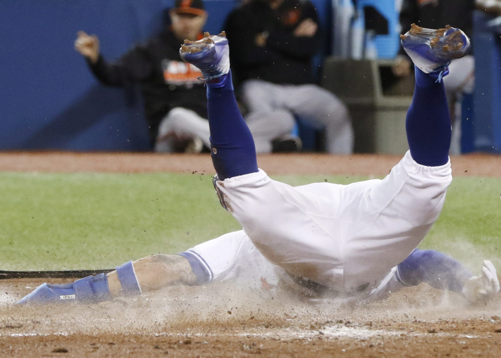 Toronto's Kevin Pillar slides home during the fifth inning of Tuesday's 5-1 triumph over Baltimore, giving the Blue Jays a two-game lead for the first wild-card slot in the AL.